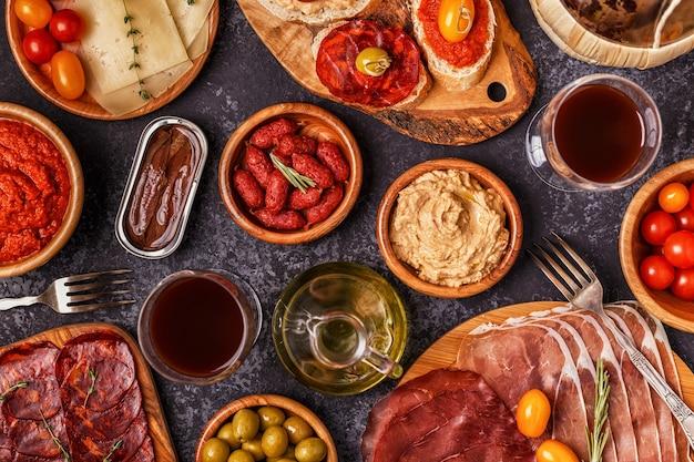 Fette di prosciutto, chorizo, salsiccia, ciotole con olive, pomodori, acciughe, purea di ceci, formaggio.