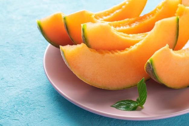 Fette di melone cantalupo succoso su un piatto.