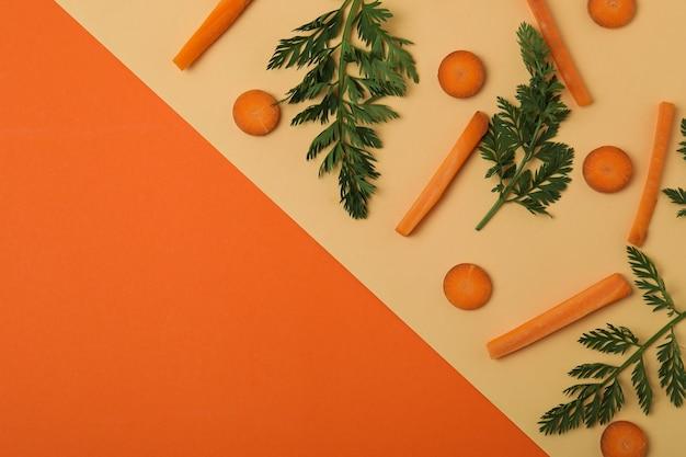 Fette e foglioline di carota fresca su superficie bicolore