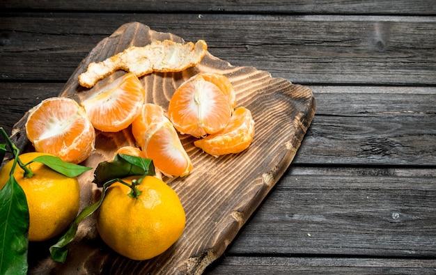 Fette di mandarini sul tagliere. sullo sfondo di legno