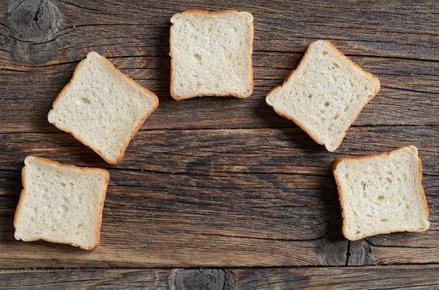Fette di mini toast su un vecchio sfondo di legno, vista dall'alto