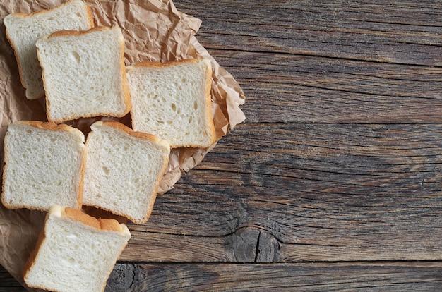 Fette di mini toast su carta su un vecchio tavolo in legno vista dall'alto con spazio per le copie