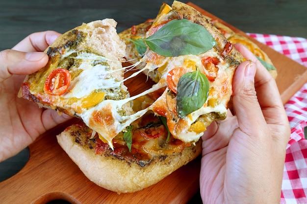 Fette di deliziosa pizza vegetariana al pesto con formaggio fuso allungato nelle mani