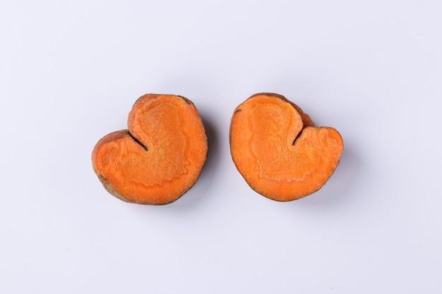 Fette di carote organiche a forma di cuori, concetto per il giorno di san valentino, amore-carote, primo piano, vista dall'alto