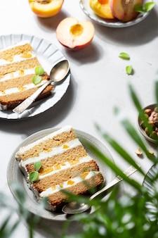 Fette di torta di pesche con crema al burro e miele su fondo chiaro