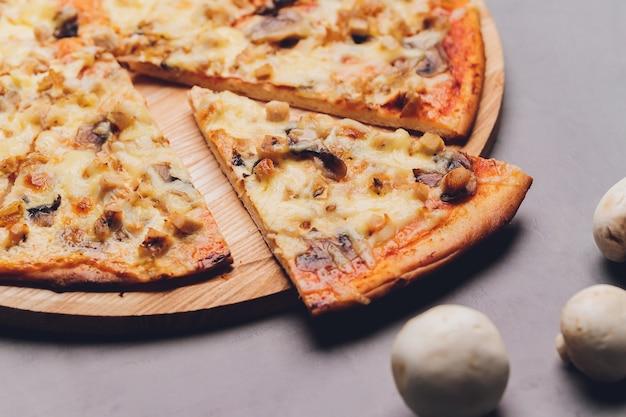 Fette di pizza su vassoio in legno rustico e sfondo scuro.