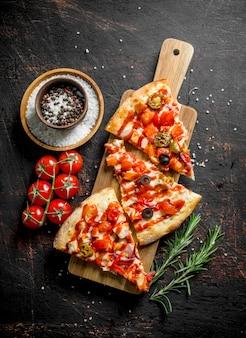 Fette di pizza con spezie, pomodori e rosmarino. su fondo rustico scuro