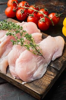 Fette di filetti di carne di pollo crudi, sul vecchio fondo di legno scuro della tavola