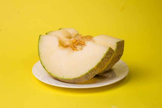 Fette di melone maturo su un piatto su sfondo giallo