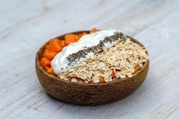 Fette di frutta matura dolce papaia con fiocchi d'avena, semi di chia e yogurt bianco sulla ciotola di cocco