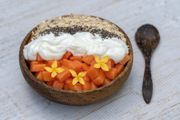 Fette di frutta matura papaya dolce con fiocchi d'avena, semi di chia e yogurt bianco sulla ciotola di cocco