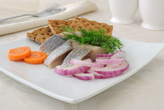 Fette di filetto di aringa salata con cipolla