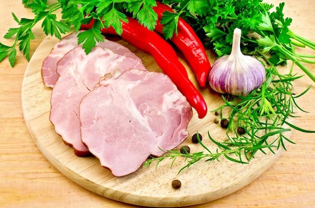 Fette di maiale affumicato, peperoncino, aglio, prezzemolo, dragoncello su una tavola di legno rotonda