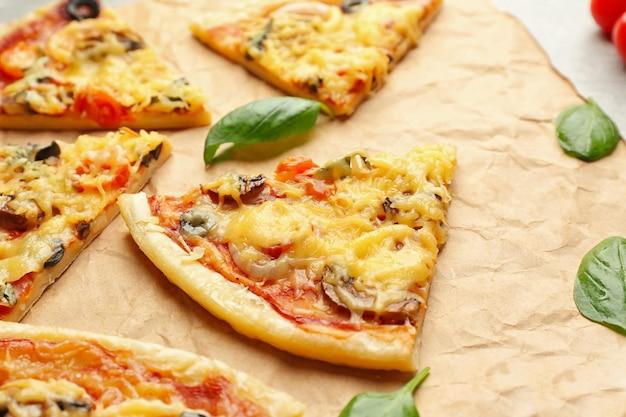 Fette di gustosa pizza su pergamena, primo piano