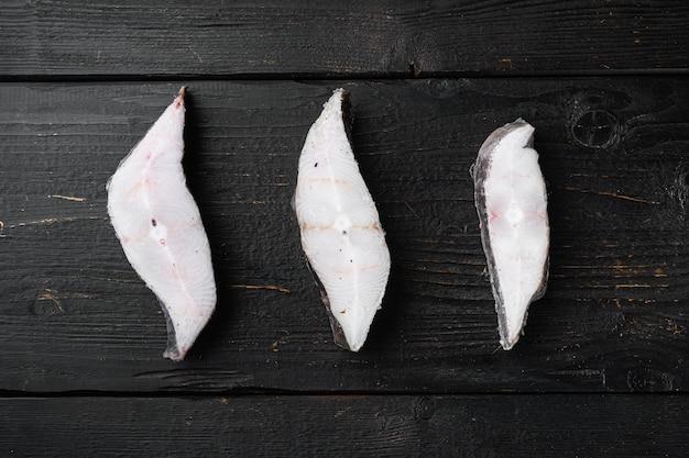 Fette di pesce bianco insieme del mercato dei frutti di mare, sul fondo di legno nero della tavola, disposizione piana di vista superiore