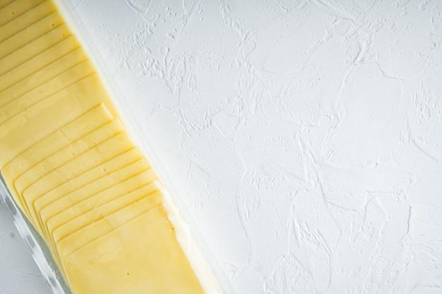 Fette di formaggio giallo in confezione sigillata, sul tavolo bianco