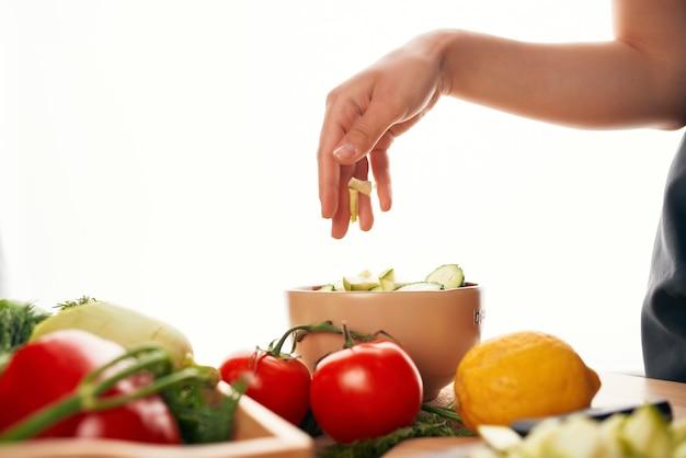 Affettare gli ingredienti delle verdure fresche per il cibo sano dell'insalata in cucina