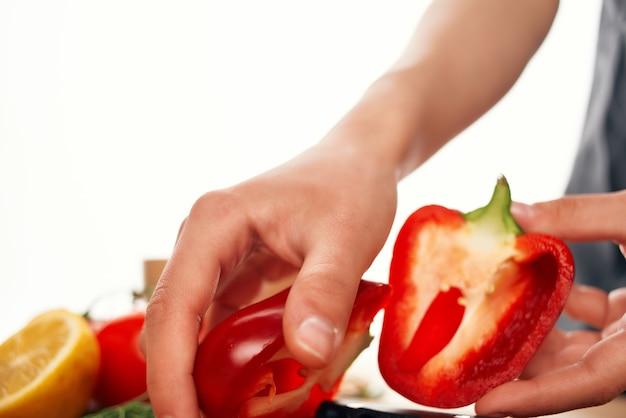 Affettare i peperoni rossi su una cucina del tagliere che cucina il primo piano dell'alimento