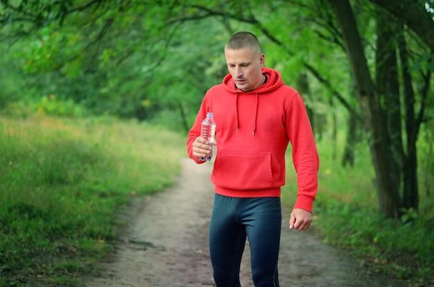 Un corridore atletico snello in una giacca rossa con cappuccio e leggins sportivi neri tiene in mano una bottiglia d'acqua dopo aver fatto jogging su una foresta verde primaverile.