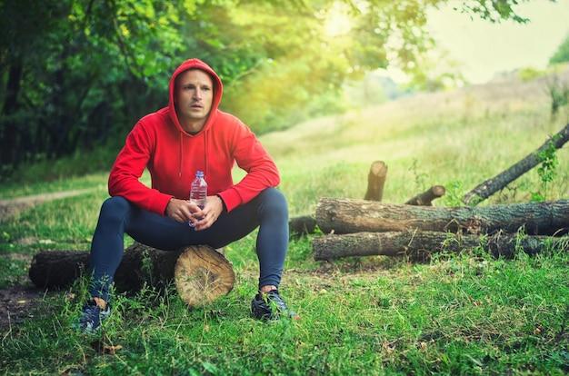 Un corridore atletico sottile in una giacca sportiva rossa con cappuccio e leggings neri si siede su un tronco e tiene una bottiglia con acqua dopo aver corso su una foresta verde primaverile.