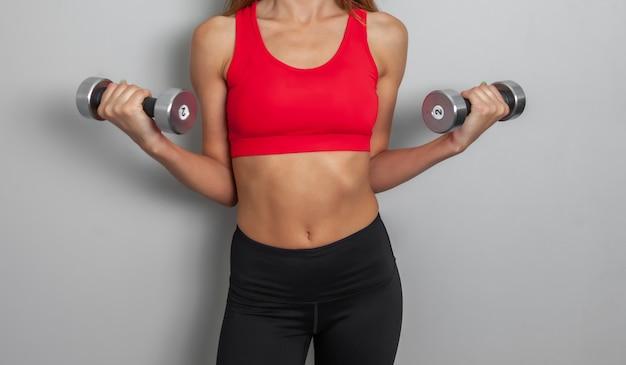 La donna sportiva esile e attraente in un top sportivo rosso si sta esercitando con i manubri nelle sue mani su uno sfondo grigio. stile di vita sano, concetto di fitness