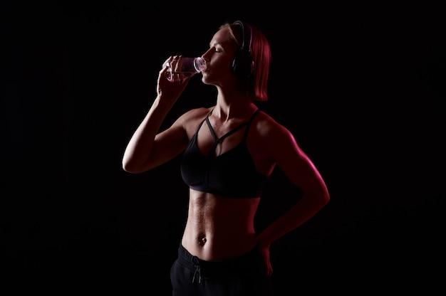 La donna magra e attraente in abiti sportivi con le cuffie beve acqua dopo l'allenamento su sfondo nero isolato