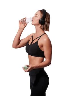 La donna attraente esile in abiti sportivi con l'acqua della bevanda dell'asciugamano dopo l'allenamento su fondo bianco
