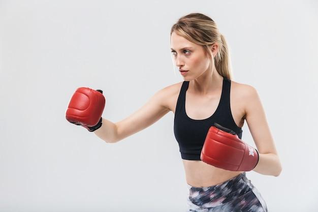 Slim donna bionda vestita di abbigliamento sportivo e guantoni da boxe che si allenano e durante il fitness in palestra isolate su muro bianco