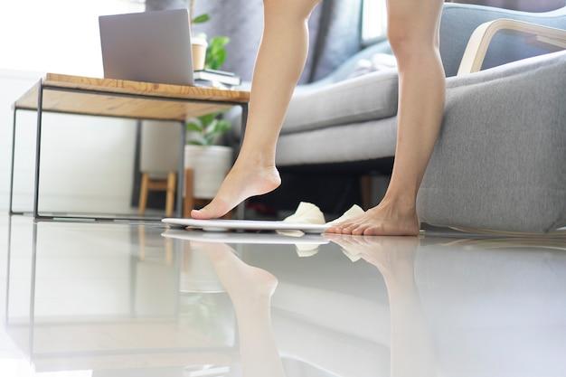 Corpo femminile sottile uso bilancia peso a casa