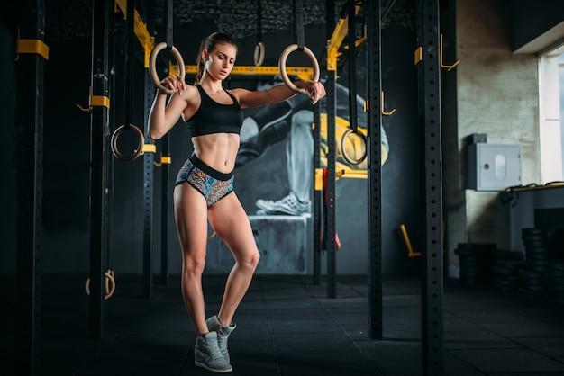 Esercizio di atleta femminile sottile su anelli di ginnastica