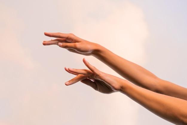 Mani femminili sottili contro il cielo ballando balletto