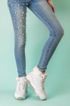 Piedini femminili sottili in jeans stretti e scarpe da ginnastica bianche su una superficie blu