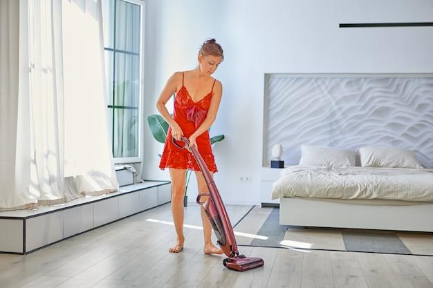 Donna magra in vestaglia con aspirapolvere pulisce la stanza