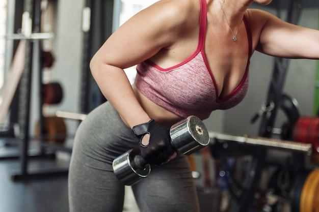 Donna slim fit che pratica l'estensione di un braccio con un manubrio inclinato.