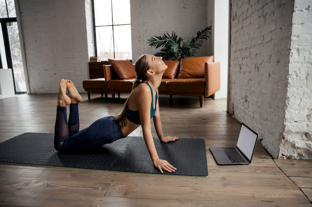 Donna slim fit che pratica yoga e allunga il corpo a casa utilizzando il laptop per lezioni online o tutorial virtuali. foto di alta qualità