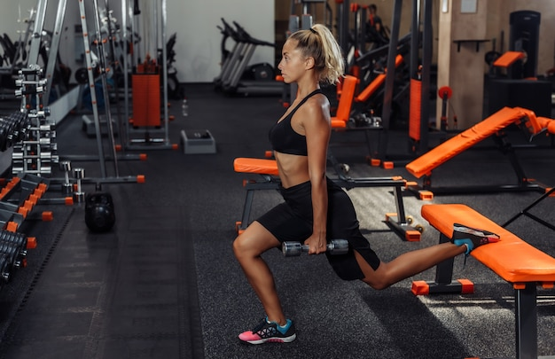 Slim fit donna in abiti sportivi praticando affondi con manubri in mano in palestra. concetto di allenamento con pesi liberi. allenamento funzionale