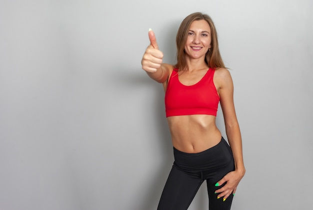 Donna slim fit in abbigliamento sportivo che mostra pollice in su su sfondo grigio