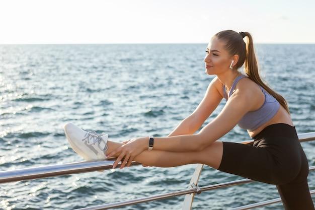 Una donna snella con un corpo perfetto sta praticando l'allungamento delle gambe prima dell'allenamento sulla spiaggia all'alba