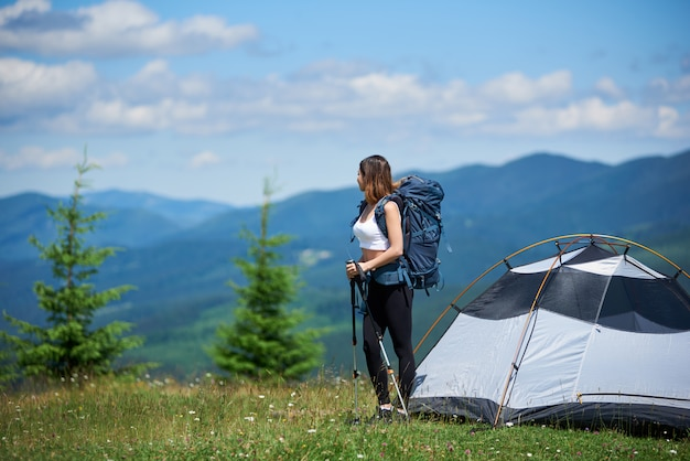 Slim girl climber con zaino e bastoncini da trekking vicino alla tenda sulla cima di una collina contro il cielo blu e nuvole, guardando lontano, riposando dopo l'arrampicata, godendo la giornata di sole in montagna