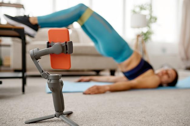 Ragazza sottile che fa esercizio di stretching a casa, formazione in linea in forma al computer portatile. persona di sesso femminile in abbigliamento sportivo, allenamento sportivo internet, interno della stanza