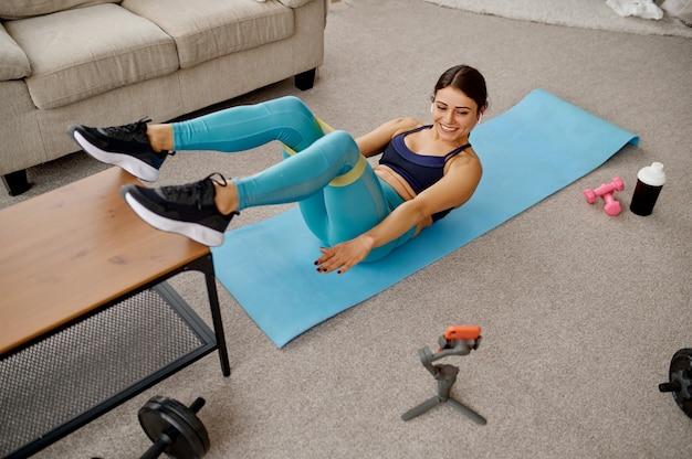 Ragazza sottile che fa esercizio di stretching a casa, formazione in linea in forma al computer portatile