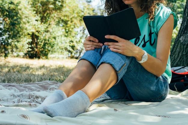 Ragazza esile in jeans e una maglietta che legge un libro in un parco che si siede su una coperta