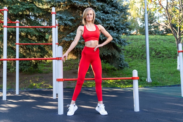 Slim ragazza in abiti fitness rossi in posa sul campo sportivo di strada