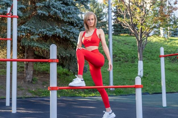Slim ragazza in abiti fitness rossi lavora sul campo sportivo di strada