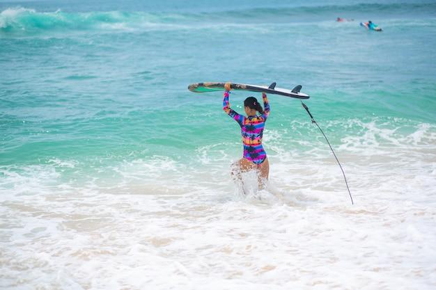 Ragazza sottile a cavallo sulla tavola da surf nell'oceano. stile di vita sano e attivo nella vocazione estiva.