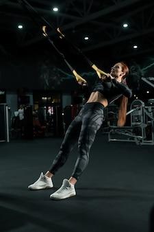 Slim ragazza in abiti sportivi che esercitano sulla vista del simulatore