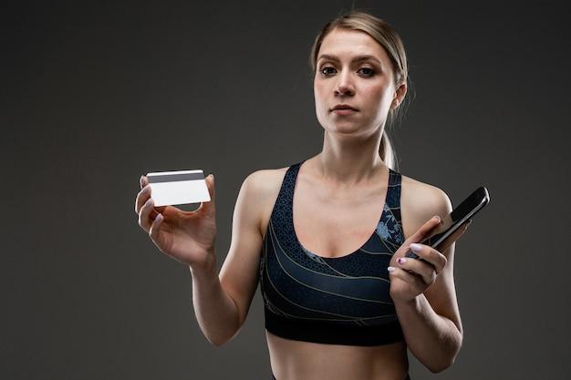 Ragazza esile in abiti sportivi con una carta di credito e un telefono su una parete nera