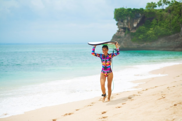 Ragazza sottile con tavola da surf sulla spiaggia di sabbia tropicale. stile di vita sano e attivo nella vocazione estiva.