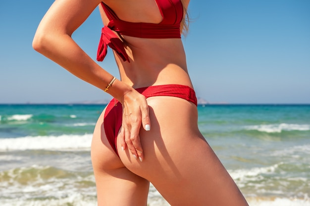 Ragazza sottile di lusso in un bikini rosso sulla spiaggia.