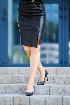 Piedini femminili sottili e muscolosi in gonna di pelle scendendo le scale vicino all'edificio per uffici